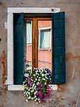 Window flower box and reflection, along Fondamenta dei Vetrai on the main canal of Murano, Italy