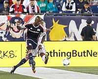 New England Revolution forward Dimitry Imbongo (92) passes the ball as D.C. United defender Ethan White (15) defends. In a Major League Soccer (MLS) match, the New England Revolution (blue) defeated D.C. United (white), 2-1, at Gillette Stadium on September 21, 2013.