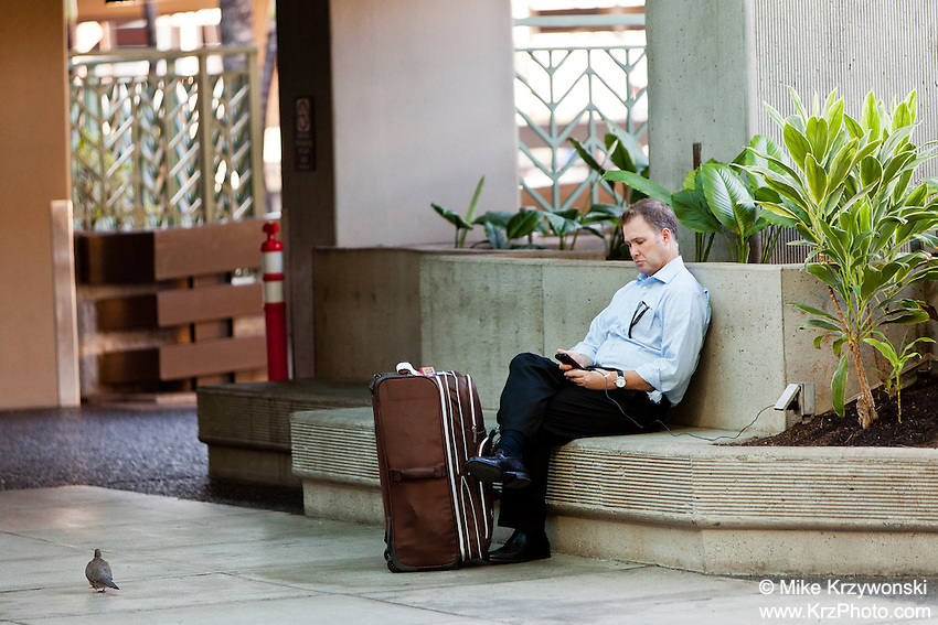 Caucasian businessman w/ luggage checking cell phone at the Honolulu International Airport, Oahu, Hawaii