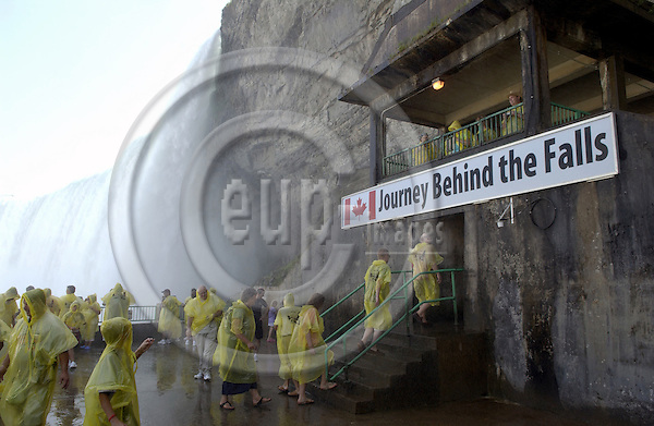 Niagara Falls, Ontario, Canada - 01 August 2006---Tourists / visitors equipped with yellow plastic coats against the mist at the entrance to the Journey Behind the Falls (Horseshoe Falls, on the Canadian side) ---nature, people, tourism---Photo: Horst Wagner / eup-images
