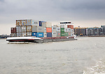 Heavily laden container ship 'Factotum' passing housing on the River Maas, Port of Rotterdam, Netherlands