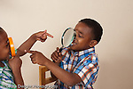 3 year old and 6 year old brother having fun looking at each other through magnifying glasses horizontal