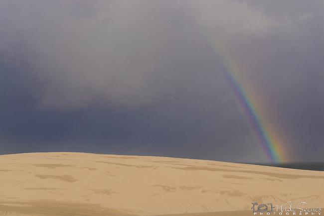 Rainbow amongst the sand dunes. Stockton Beach Sand dunes Worimi Conservation Lands. Anna Bay, Port Stephens, NSW, Australia.