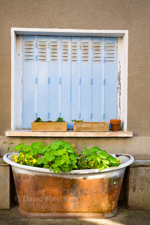 A closed window and flowers in an old bath tub in the town of Tournon-d'Agenais, situated in the Lot-et-Garonne, Aquitaine region, in the south-west of France.