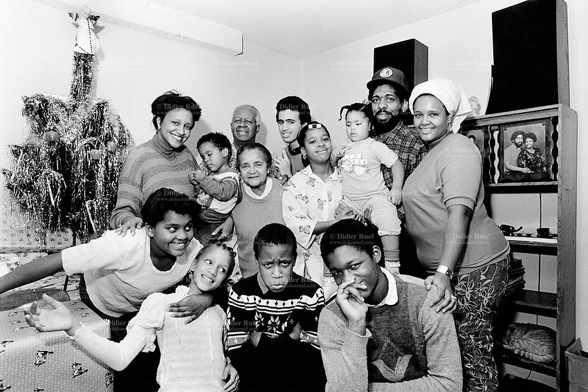"""USA. New York City. Spanish Harlem. Portrait of a Puerto Rican family and the Christmas tree. Family portrait with three generations: (bottom left to right) Bente, Sala, Willie and Richie. (Up left to right) Nina, Papo, grandfather Alejandro, grandmother Juanita, Carlos, Lady, Chichi, Tito and Pat. The family lives below the poverty line and receives public assistance (AFDC, Home Relief, Supplemental Security Income and Medicaid). The family resides in units managed by the New York City Housing Authority (NYCHA) which provides housing for low income residents. NYCHA administers rental apartments in facilities, popularly known as """"projects"""". Spanish Harlem, also known as El Barrio and East Harlem, is a low income neighborhood in Harlem area. Spanish Harlem is one of the largest predominantly Latino communities in New York City. 24.12.86 © 1986 Didier Ruef .."""