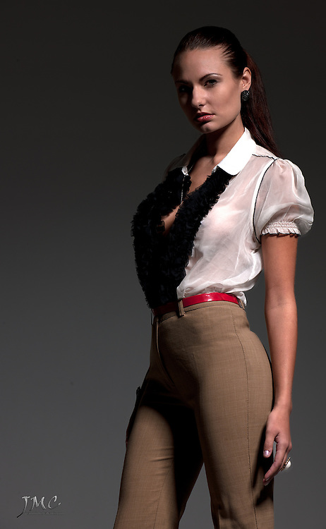 Beautiful brunette fashion model in white blouse, brown pants, red belt