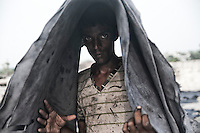 Iqbal (19) is carrying leather on his head at a tannery in Jajmau area, Kanpur. Exposure to the harmful chemicals used in the tannery causes skin diseases, respiratory diseases, gastro-intestinal ailments etc. Researches have shown presence of elevated amount of chromium in the blood and urine of the workers. Kanpur, Uttar Pradesh, India. Arindam Mukherjee
