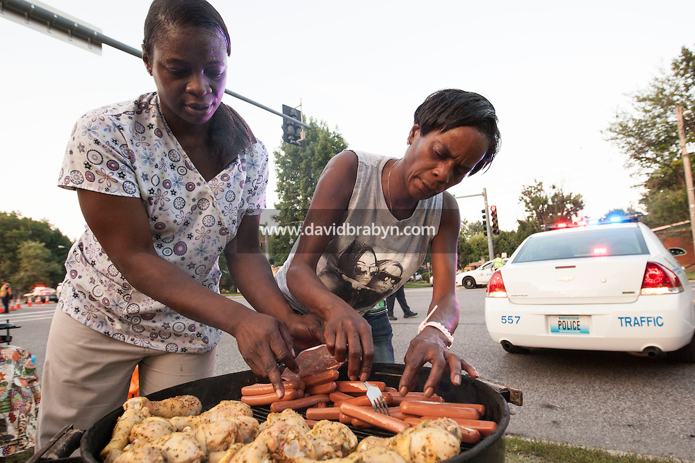 HSUL 20140818 United States, Ferguson, MO. Kimberly Anderson (L) and Peraisee Moore barbecue food for passers-by alongside a police road barrage on West Florissant Avenue in Ferguson, Missouri, on August 18, 2014. Photographer: David Brabyn
