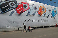 A cyclist passes a huge Olympus digital cameras advertisement billboard in Beijing, China..20-APR-05
