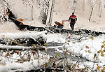 Workers work to clear a large tree that completed blcked the entrance to the High Manor Trailer Park in Vernon, after the record breaking snow storm brought down trees and utility wires leaving more than 700, 000 CL+P customers in the dark, Sunday, October 30, 2011. (Jim Michaud/Journal Inquirer).