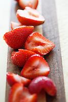 Sliced Fresh Strawberries on a Striped Cutting Board.