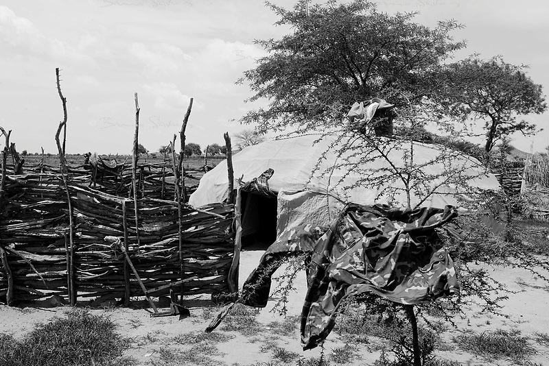 Mastariya, North Darfur, August 13, 2004.In front of a Janjaweed home: his khaki uniform drying up in the sun...