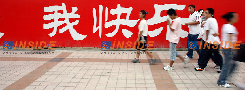Pechino Cina 19/7/2007<br /> Passanti in Wangfujing, la principale via dello shopping di Pechino. Sullo sfondo parte della scritta &quot;io partecipo, io contribuisco, io sono felice&quot;, uno degli slogan delle olimpiadi di Pechino 2008.<br /> Foto Andrea Staccioli Insidefoto