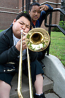 Asian teen musician playing trombone at Ramsey school after parade performance. Grand Old Day Festival. St Paul Minnesota MN USA