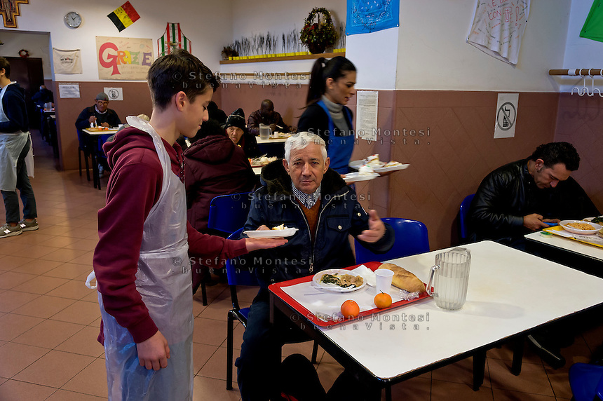 ROME, ITALY  -  DECEMBER 17:   Volunteer offers  to a guest  the cake offered by Pope Francis to the poor of the Colle Oppio canteen. Pope Francis celebrates 80 years with 1500 guests of Rome's Caritas, offering cakes to be included in the menu with the meal that is delivered on December 17, 2016 in Rome, Italy.