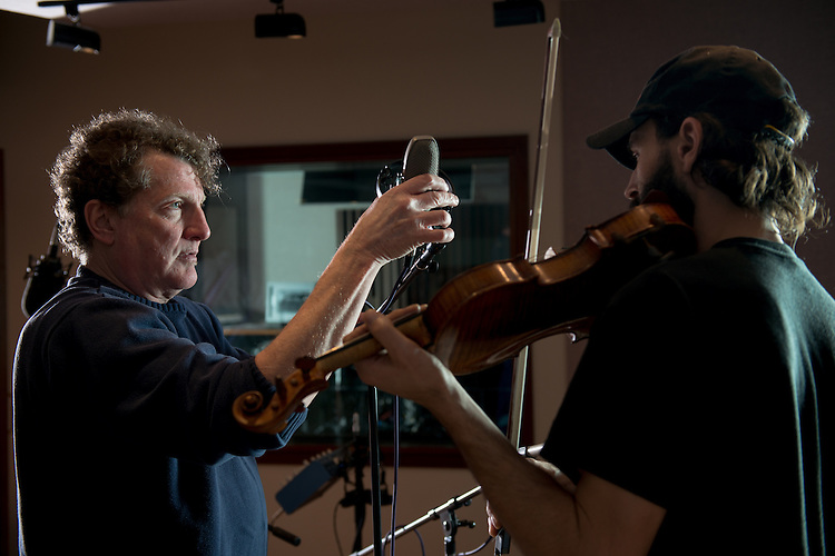 Eddie Ashworth adjusts the position of a microphone for musician Willie Perkins in between tracks during a recording session at MDIA Sound.