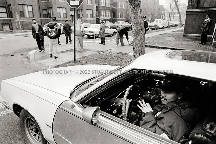 10/1994--Chicago, USA..Ricky, the OLB gang leader, flashes a gang sign at the corners of Argyle and Glenwood Streets on Chicago's Northside, while other OLBs hang out. All 4 buildings on the corner are filled with Cambodian families, it is the heart of the OLB's (Original Loco Bloods) turf...©2008 Stuart Isett.All rights reserved