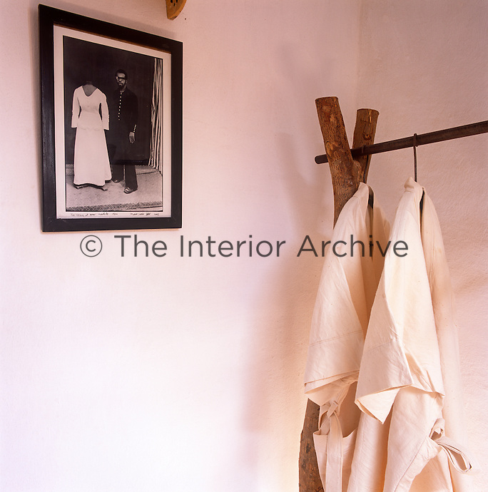 Two white cloth dressing gowns hang from a pole set between to upright posts.