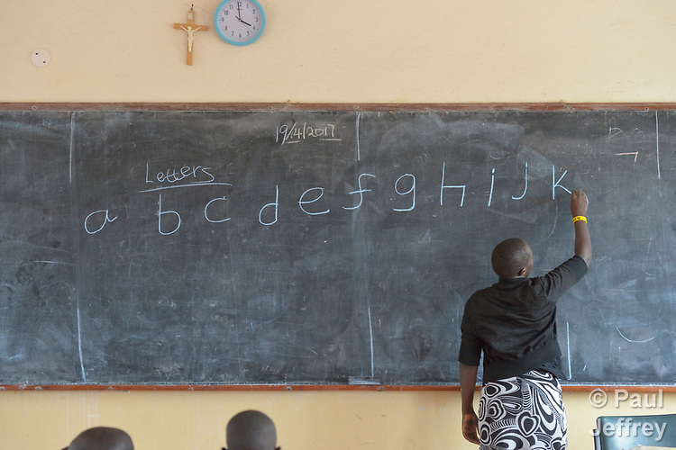 A teacher writes on the blackboard in the Loreto Primary School in Rumbek, South Sudan. The Loreto Sisters began a secondary school for girls in 2008, with students from throughout the country, but soon after added a primary in response to local community demands.