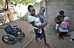 Eric Lovemore, 8, gets carried into his house in Bulawayo, Zimbabwe, by his stepmother, Zandile Tohori. Lovemore suffered cerebral palsy and uses a wheelchair provided by the Jairos Jiri Association with support from CBM-US.