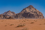 Blowing desert sand and mountains in the Wadi Rum Protected Area, a UNESCO World Heritage Site.  Um Sahn sandstone.  Hashemite Kingdom of Jordan.