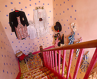 The stairs are covered in colourful Fablon and the walls, painted pink with purple spots, are covered with items of clothing hanging from hooks