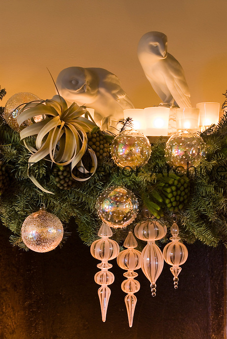 A pair of plaster-cast owls and tealights sit on the mantelpiece decorated with sprigs of spruce and glass baubles for Christmas