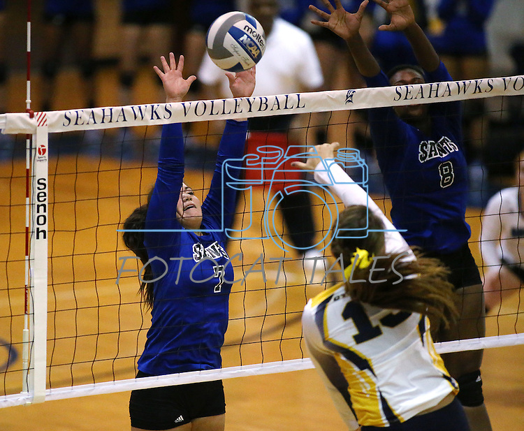 Marymount's Ashley Cabrera and Morgan McAlpin block in a college volleyball game against St. Mary's in Lexington Park, MD, on Wednesday, Oct. 29, 2014. Marymount won 3-2 to go 24-9 on the season.<br /> Photo by Cathleen Allison