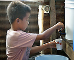 Kent Arthur Quintana, 11, gets clean water from a water filter in his temporary home in Tanauan, a city in the Philippines province of Leyte that was hit hard by Typhoon Haiyan in November 2013. The storm was known locally as Yolanda. Hundreds of families here received water filters from the United Methodist Committee on Relief, a member of the ACT Alliance. UMCOR is also working with city officials to help residents here build permanent houses to replace those they lost in the storm.