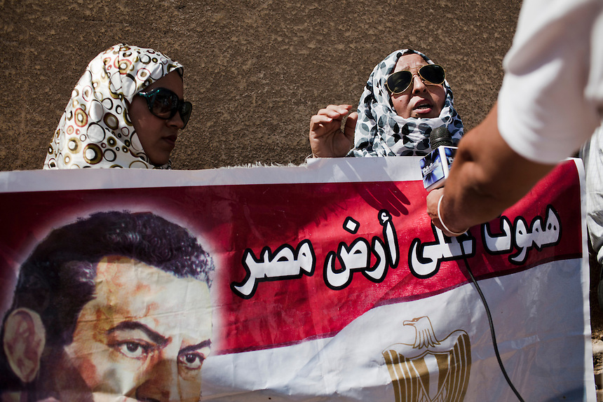 Supporters of former Egyptian President, Hosni Mubarak, talk to the media while waiting to hear the verdict in his trial in front of the Cairo Police Academy, Egypt, June 2, 2012. Photo: ED GILES.