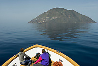ITA, Italien, Sizilien, Liparischen Inseln, Insel Alicudi: das Ausflugsboot naehert sich der westlichsten Insel im dunstigen Morgenlicht | ITA, Italy, Sicily, Aeolian Islands or Lipari Islands, island Alicudi: excursion boat approching the most western island at misty morning light