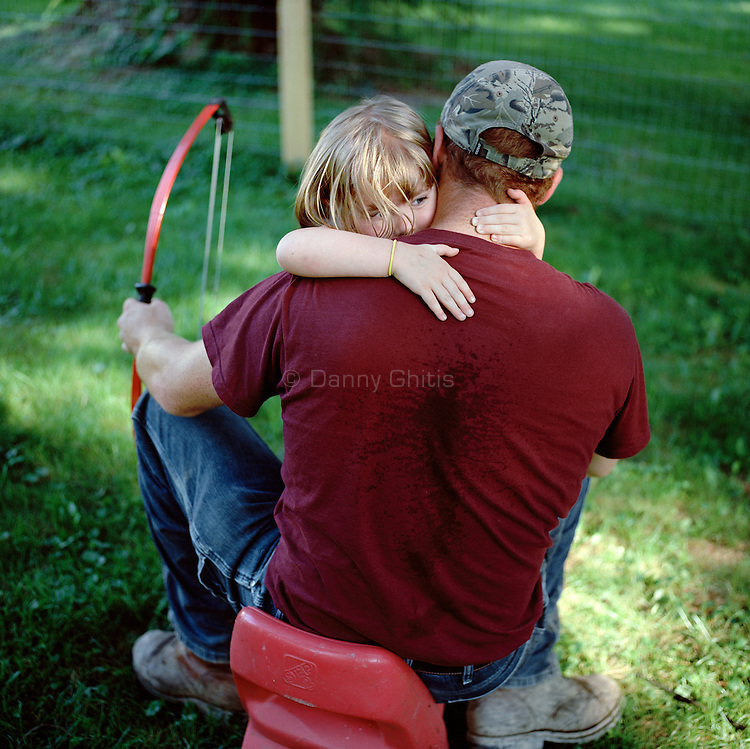 Father and daughter hug in between arrows at their home in Dutchess County.