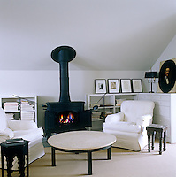 In the sitting room of a converted carriage house in upstate New York a cheerful glow comes from the cast-iron stove