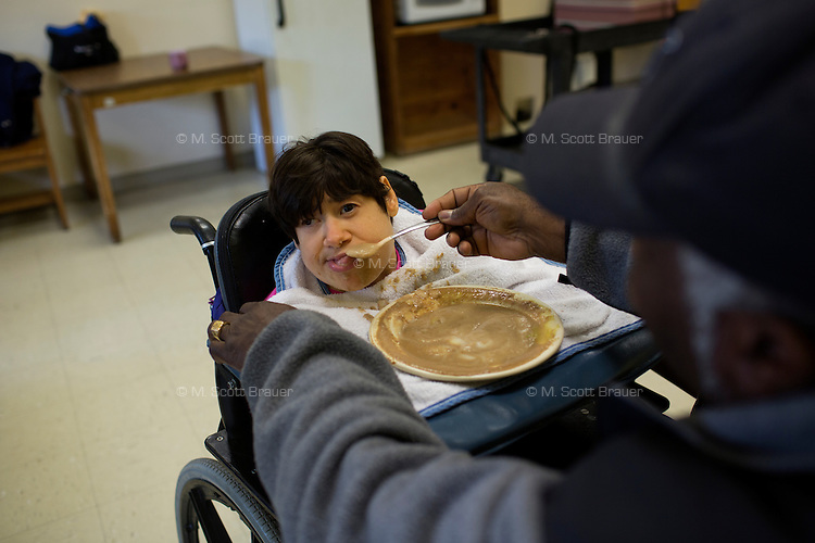 Caretakers help Fernald resident Teresa Kacinski eat lunch at the Fernald Developmental Center in Waltham, Mass., USA.