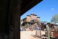 """Goldfield Ghost Town in Goldfield, Arizona is located 40 miles southeast of Phoenix -at the base of the Superstition Mountains- and it has been called """"Gateway to the Superstition Mountains."""" Thanks to the discovery of gold in 1892, the town turned into a booming community with a population of four to five thousand people. Facilities included a hotel, a general store, three saloons, boarding houses, a blacksmith, a school house, a hotel, a meat market and a brewery. The mining district had at one point 50 gold mines. While Goldfield's growth and wealth was promising, a decrease in the gold deposits caused Goldfield to decline. Further attempts to bring back Goldfield to its thriving days between 1910 and 1926 failed. Today, Goldfield Ghost Town is a very interesting Arizona tourist spot that draws thousands of visitors a year with attractions like a tour to the underground mines, a ride in the only Arizona-operating narrow gauge train, a Main Street with retail shops, Old West buildings, a Gold Panning shop, and a museum among others. The Goldfield Superstition Museum offers visitors various exhibits about the town and nearby geology. Old mining machinery, tools and artifacts and old vehicles give the impression that time stopped in Goldfield, giving this town a genuine ghost-town charm. On some weekends, volunteer Old West performers offer gun fight shows. Goldfield also offers a spectacular view of Superstition Mountains. Photo by Eduardo Barraza © 2010"""