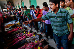 Bangladeshis walk past bodies of victims to identify relatives who died in a building collapse in Savar, near Dhaka, Bangladesh, Wednesday, April 24, 2013.