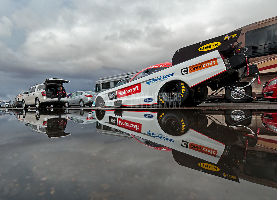 Feb 22, 2019; Chandler, AZ, USA; The car of NHRA funny car driver Bob Tasca III reflects in a rain puddle as the car is towed to the staging lanes during qualifying for the Arizona Nationals at Wild Horse Pass Motorsports Park. Mandatory Credit: Mark J. Rebilas-USA TODAY Sports