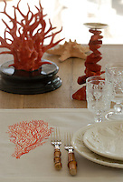 The red coral displayed on the table perfectly matches the table linen and the marine themed crockery