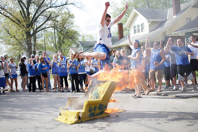 Students jumped over a burning chair on University Avenue in Lexington, Ky., on Sunday, March 25, 2012. Photo by Tessa Lighty | Staff