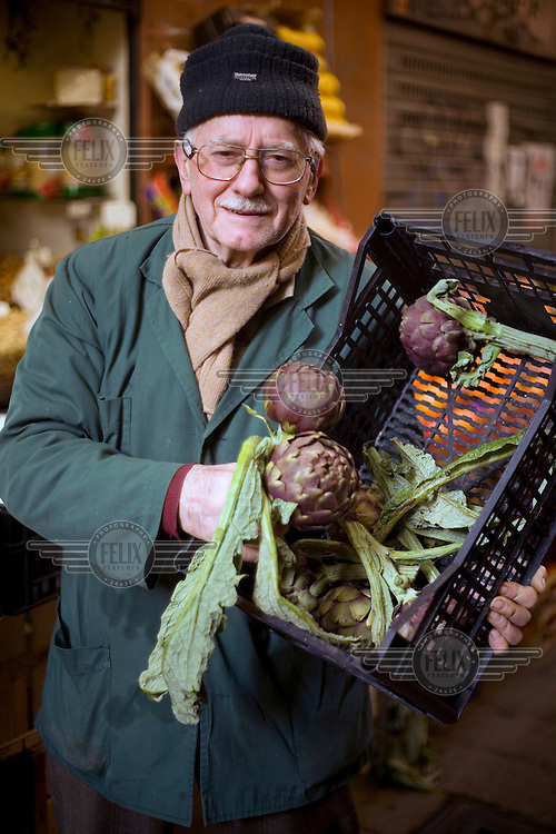 An elderly man holds a box of artichokes outside a shop in the Mercato di Mezzo in Bologna..