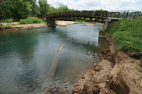 NWA Democrat-Gazette/ANDY SHUPE<br /> Damage from recent storms shows Tuesday, June 13, 2017, around the support structure of a bridge spanning Sugar Creek along the Wishing Springs Trail, a part of the Razorback Greenway in Bella Vista.