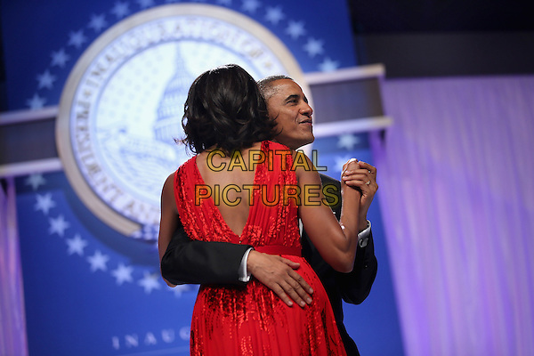 Michelle Obama & Barack Obama.2013 Inauguration Ball, Washinton D.C., USA..January 21st, 2013.half length black suit tuxedo red dress back behind rear holding hands married husband wife dance dancing arm around waist profile .CAP/ADM/CNP/CS.©Chip Somodevilla/CNP/AdMedia/Capital Pictures