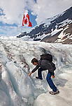 Man fills his water bottle up with glacial waters flowing from the Athabasca Glacier in the Columbia Icefields, Alberta, Canada