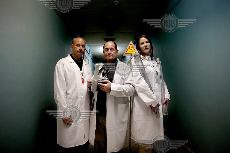 American-Ukrainian physicist Igor Bolshinsky (centre) holds a disometer, project leader Kelly Cummins (left) holds a pair of dummy fuel assemblies, and Jay Thomas (left). The removal of Kazakhstan's highly enriched uranium (HEU) is part of the U.S. Global Threat Reduction Initiative (GTRI), where Bolshinsky and Cummins work, which tries to secure nuclear material around the world to prevent their misuse.