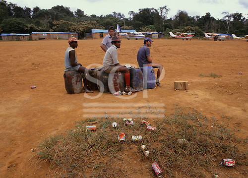 Paapiu, Roraima State, Brazil.  Goldminers on an airstrip in the Yanomami territory sitting on petrol containers, lots of cans around.