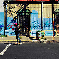 A Salvadoran young man rides a skateboard in front of a common lower middle class house, with Spanish colonial architecture elements and painted over by graffiti tags, built in the center of San Salvador, El Salvador, 14 November 2016.