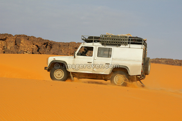 Africa, Mauritania, Sahara Desert, nr. Tidjikdja. Land Rover Defender TD5 Station Wagon crossing a sandy oued at Rachid. --- RELEASES AVAILABLE! Automotive trademarks are the property of the trademark holder, authorization may be needed for some uses.