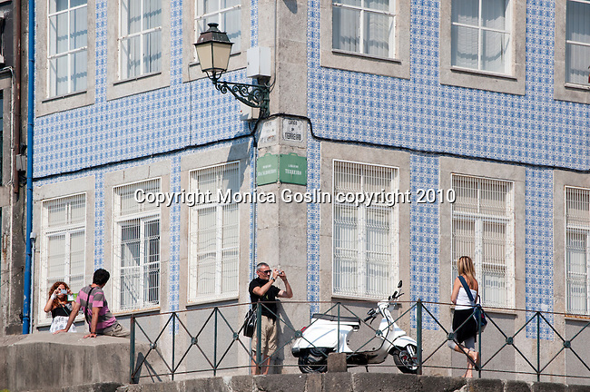 Tourists taking photos in front of a building in the Ribeira section of Porto, Portugal covered with blue and white tiles.