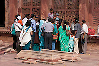 Fatehpur Sikri, Uttar Pradesh, India.  Fabric Vendor and Customers.  Visitors to the tomb of Sheikh Salim Chishti leave offerings of fabric on his grave.  Graves in foreground.