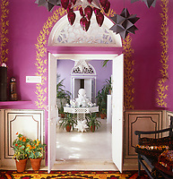 Hand-painted leaf designs adorn a doorway with a view through to the veranda